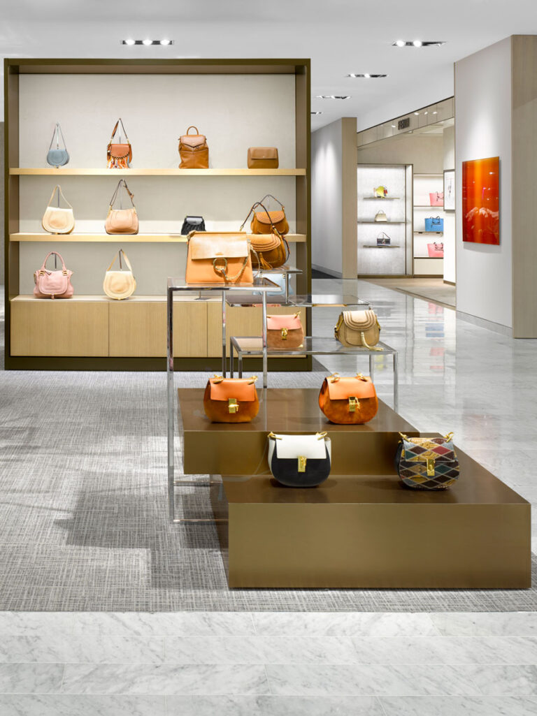 Handbag area at Neiman Marcus with pale gray marble flooring, gray carpeting, maple pedestals for purse display.