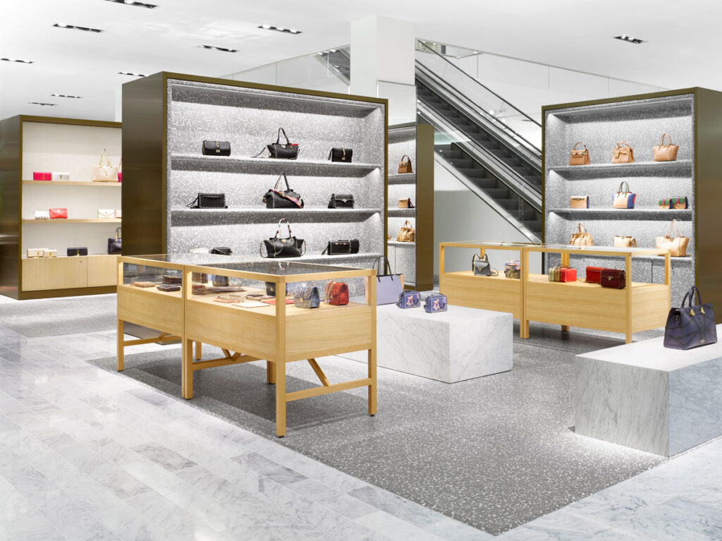 Handbag area at Neiman Marcus with purses on display, marble covered pedestals at centre with shelves of handbags set against a flecked stone background.