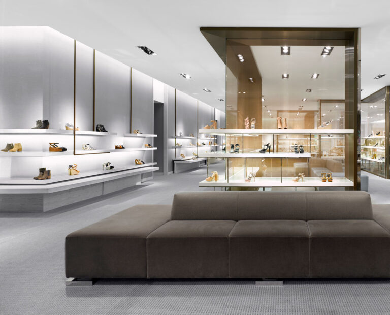 Shoe display area with white walls and white floating shelves and gray flooring. Plush gray-brown seating at centre for trying on shoes.