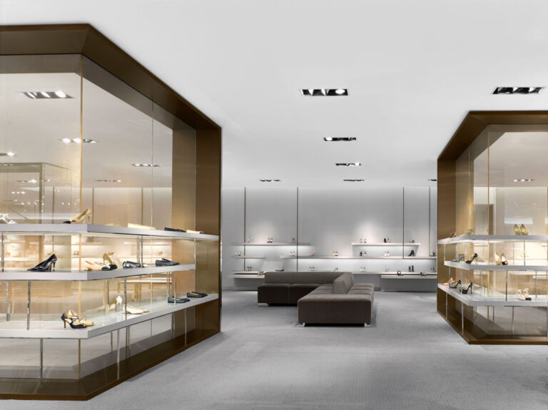 Vast open shoe area with inset lighting in ceiling and rooms created for shoes.