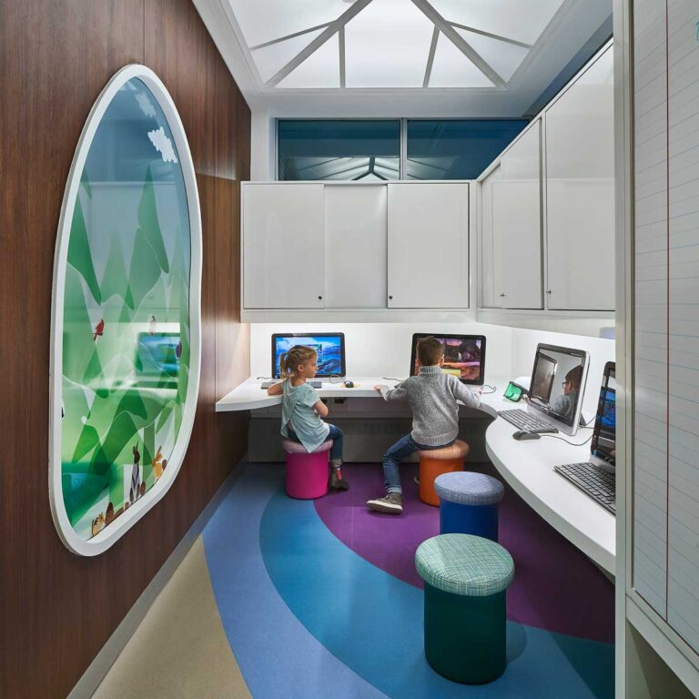Computer lab area at SickKids PlayPark, with coloured banded floor and white cabinets and skylight above. A translucent forest scene internal window is on the left wall.