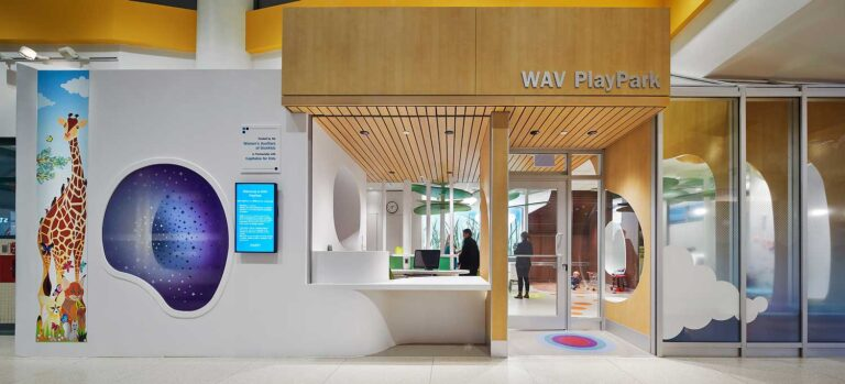 Exterior view of WAV PlayPark at SickKids Hospital with a wood facade and reception desk.