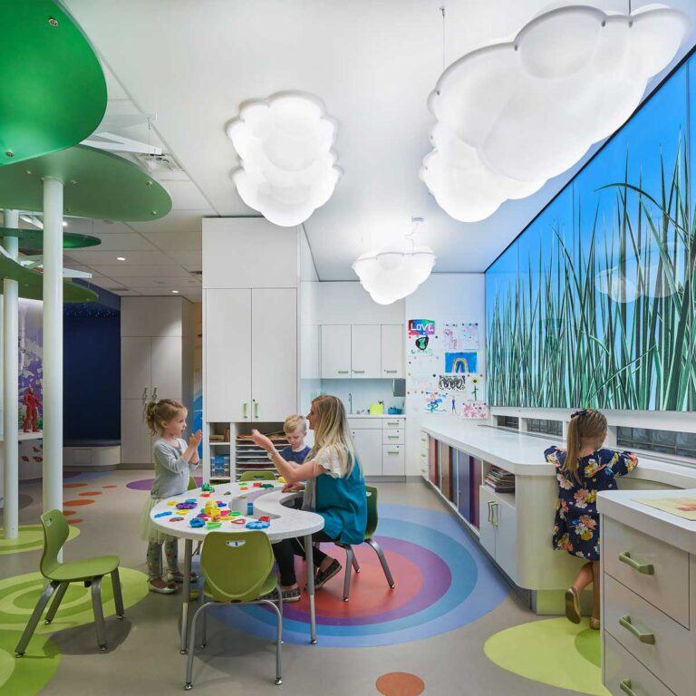 Open play area at SickKids PlayPark with cloud shaped lights, and kids playing around a table with blocks.