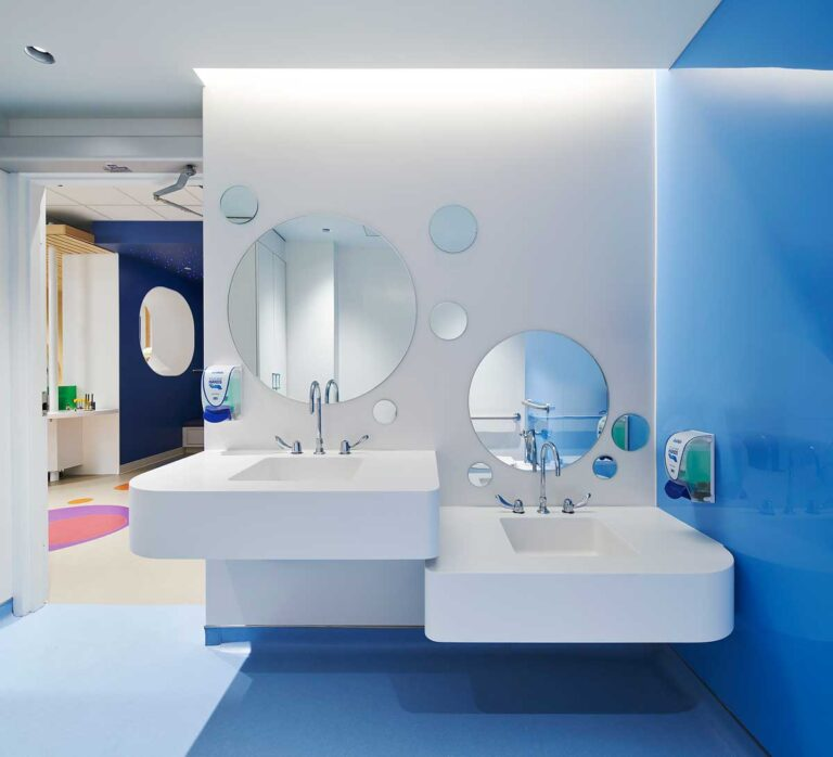 High and low floating sinks with space underneath for wheelchairs. A grouping of several round mirrors are hung above.