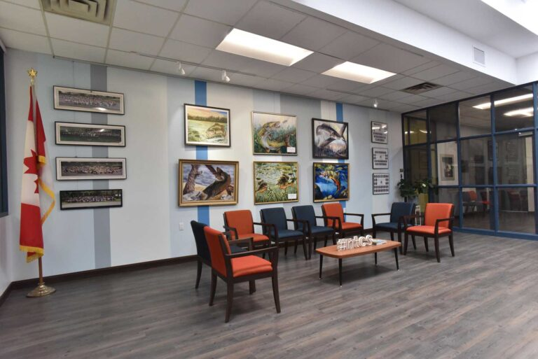 Long feature wall of artwork with orange and blue seating and gray laminate floor.
