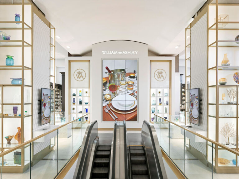 Entrance to William Ashley retail showroom with cream walls and glass and gold shelving.