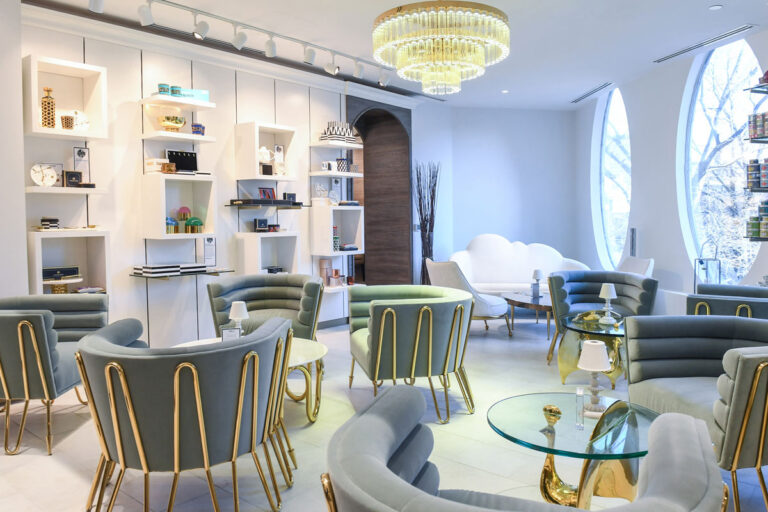 Lounge area at William Ashley with oval windows, modern crystal chandelier, sage and green tub chairs.