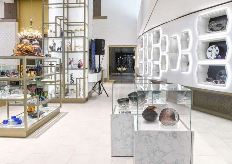 Collectibles showroom at William Ashley with gold and marble display cases, and brightly lit inset display alcoves.