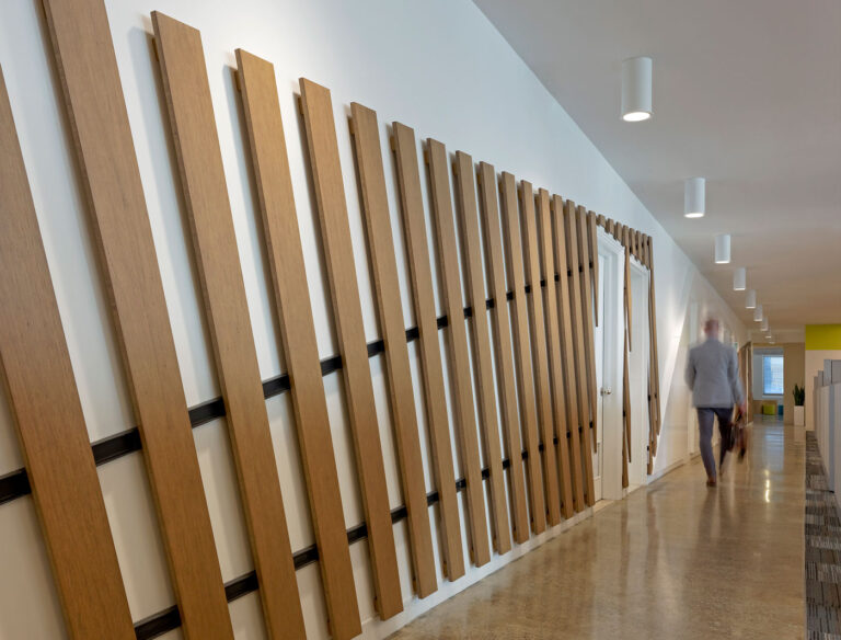 Accent wall with wood slats running diagonally over doors.