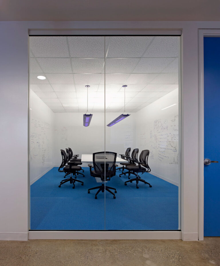 Meeting area with whiteboard walls and blue carpeting, with a wall of windows.