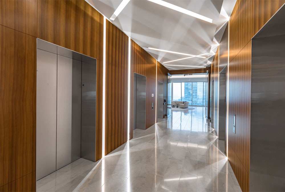 Elevator bank with wood panelled walls and diagonal lighting accents along the ceiling.