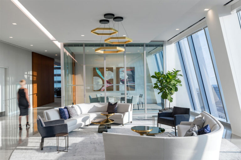 Reception area with large curved sofas, and hexagonal gold light fixtures with a private glass-walled meeting room at the far end.