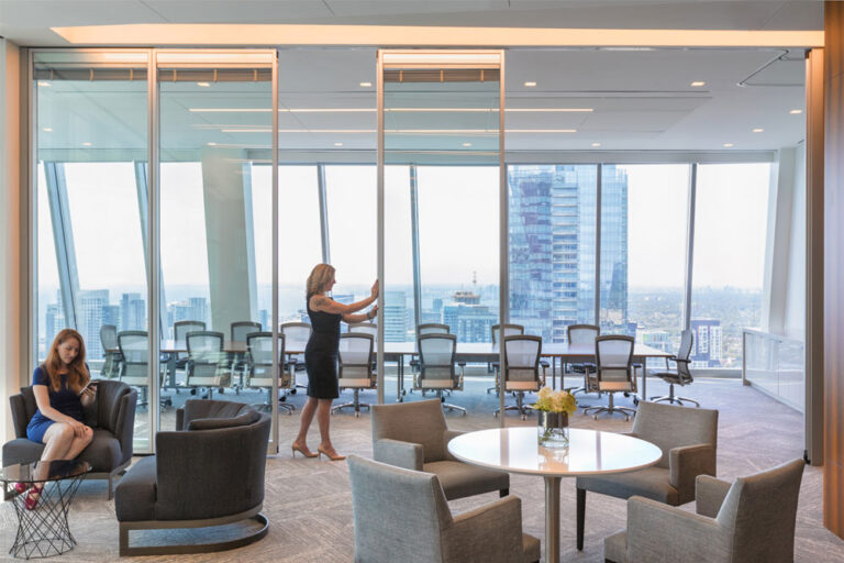 A woman pushes open the glass door to a meeting area on the 40th floor of a Toronto skyscraper.