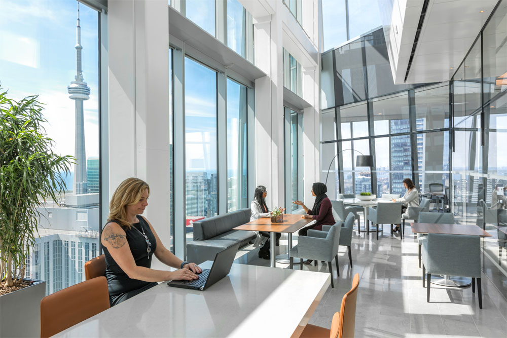 Employees at work in this bright glass panelled work space with pale limestone floors, pale teal floors and brathtaking views of Toronto.