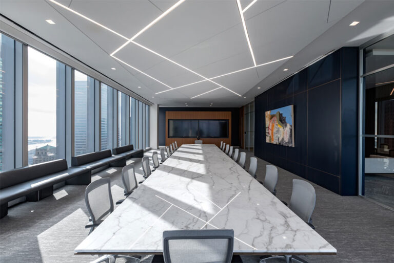 A large boardroom seats 18 or more at a large marble table with expansive city views.