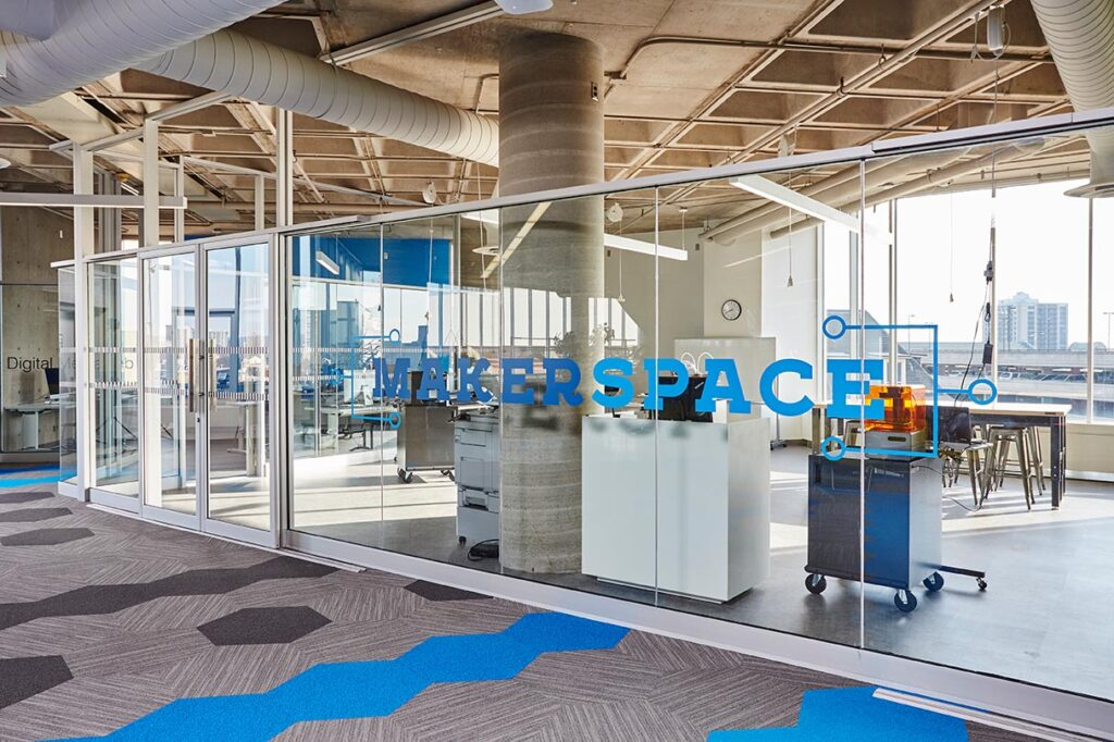 A wall of glass divides the Makerspace area from the rest of the library floor with a decal that indicates its name.