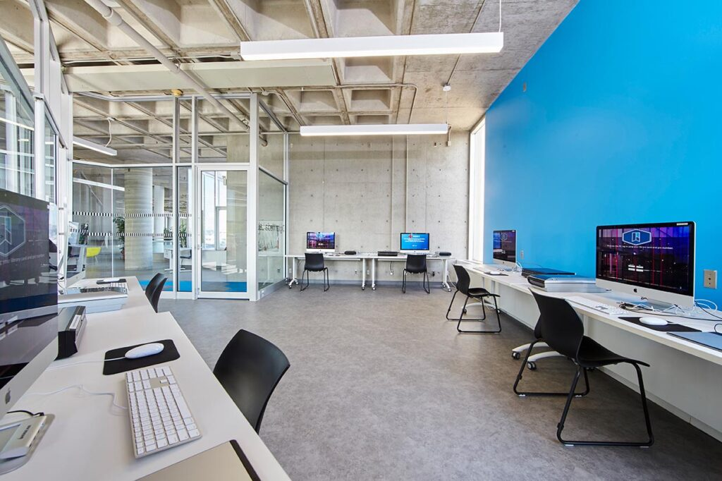 Computer lab with blue accent wall and crenelated ceiling.