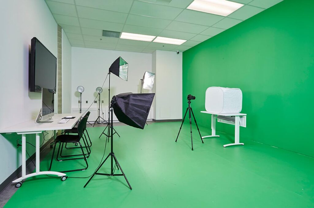 Green screen room with floor and green wall opposite editing area.