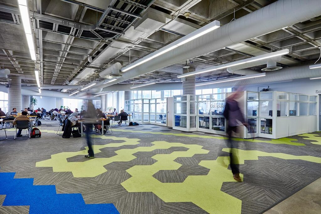View of library floor with open seating, tables and chairs and patterned carpet area.