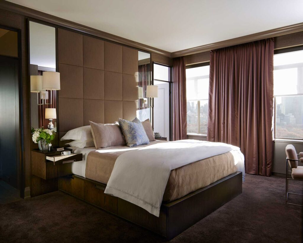 Bedroom with warm plum carpeting, soft brown curtains and padded headboard element.