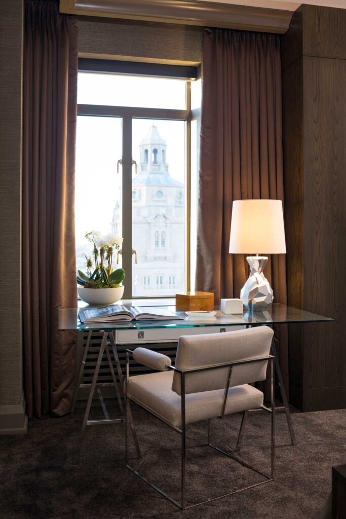Glas topped desk surrounded by cozy plum hues with a lamp and amazing view of city.