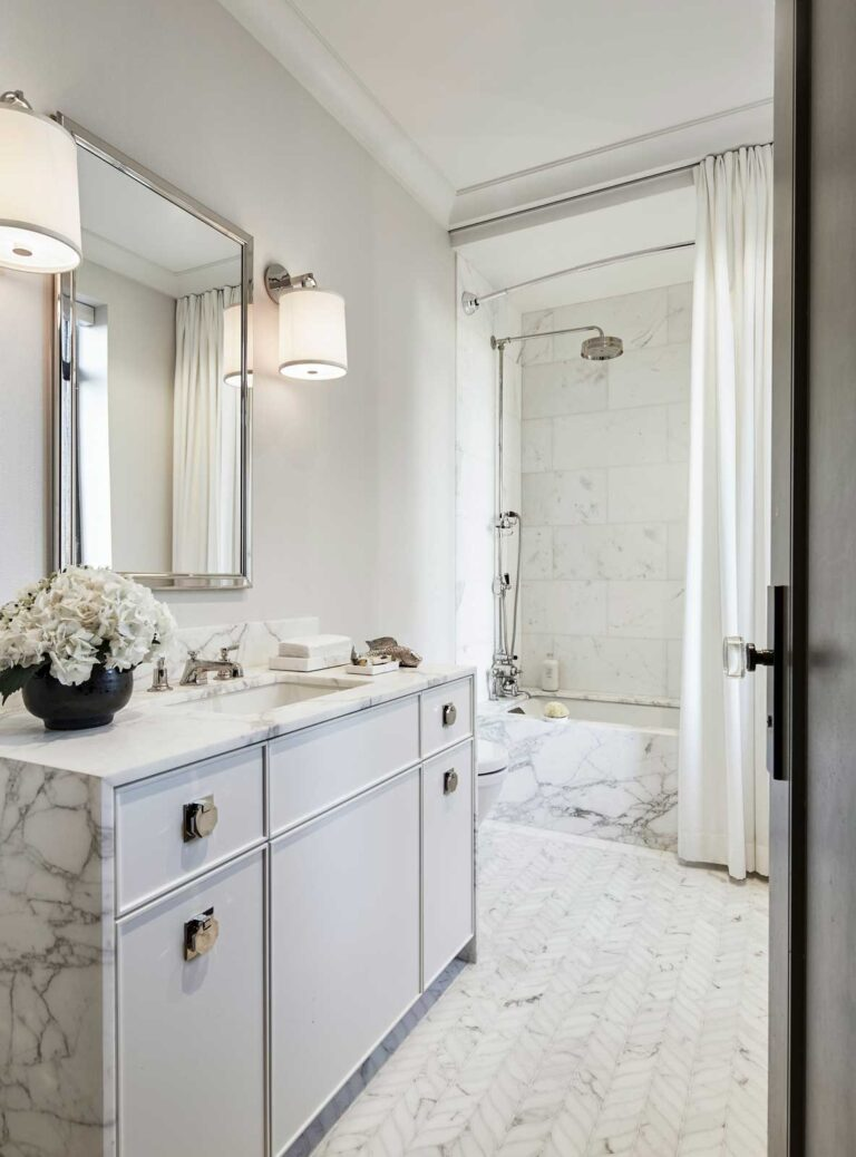 Bright white bathroom with herringbone marble flooring, and white marble topped sink, with a soaker tub and shower on the far wall.