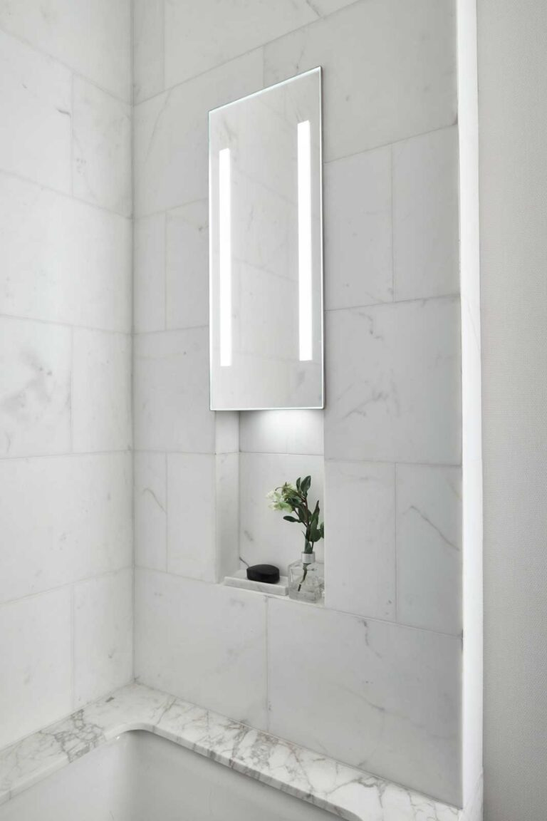 Marble lined shower and bath with illuminated shower mirror.