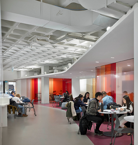 Students study at clusters of tables in the plenary cafe space with white ceiling, ductwork and gray and purple flooring.