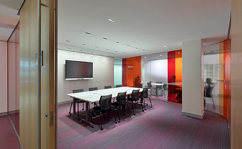 Meeting room with transparent coloured film on glass walls.
