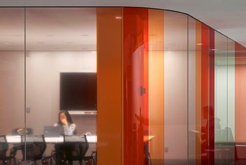 Detail of orange and rasperry coloured transparent film on windows.