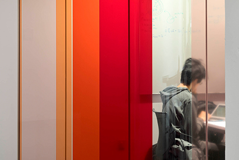 A student studies at a desk near a glass wall with coloured transparent window film.