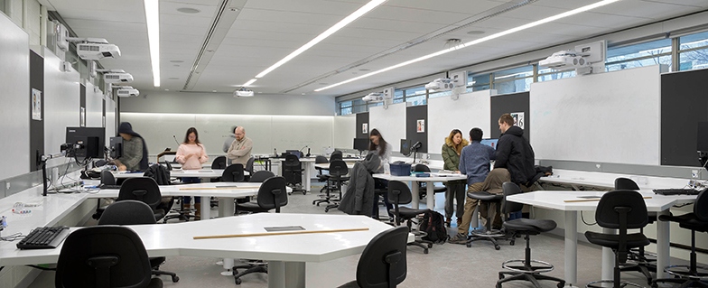 Classroom at Mclennan Physics Lab, with white walls and ceilings and whiteboards and cork boards on walls