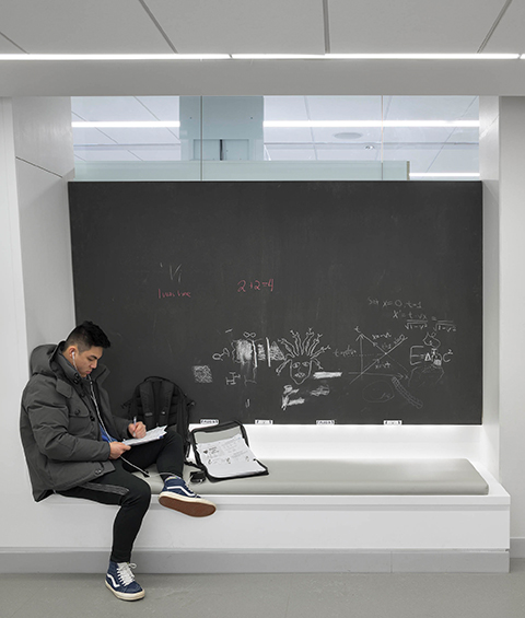 A student sits at an alcove with a blackboard in behind.