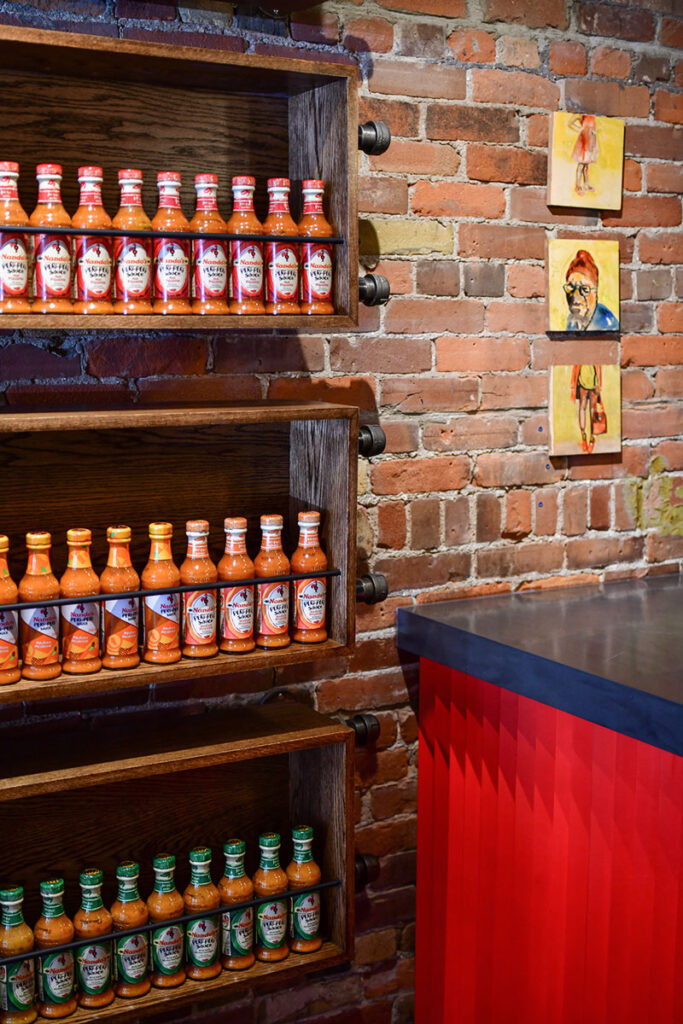 Dark wood shelves contain bottles of the brand's important sauces against a modern red and slate counter.