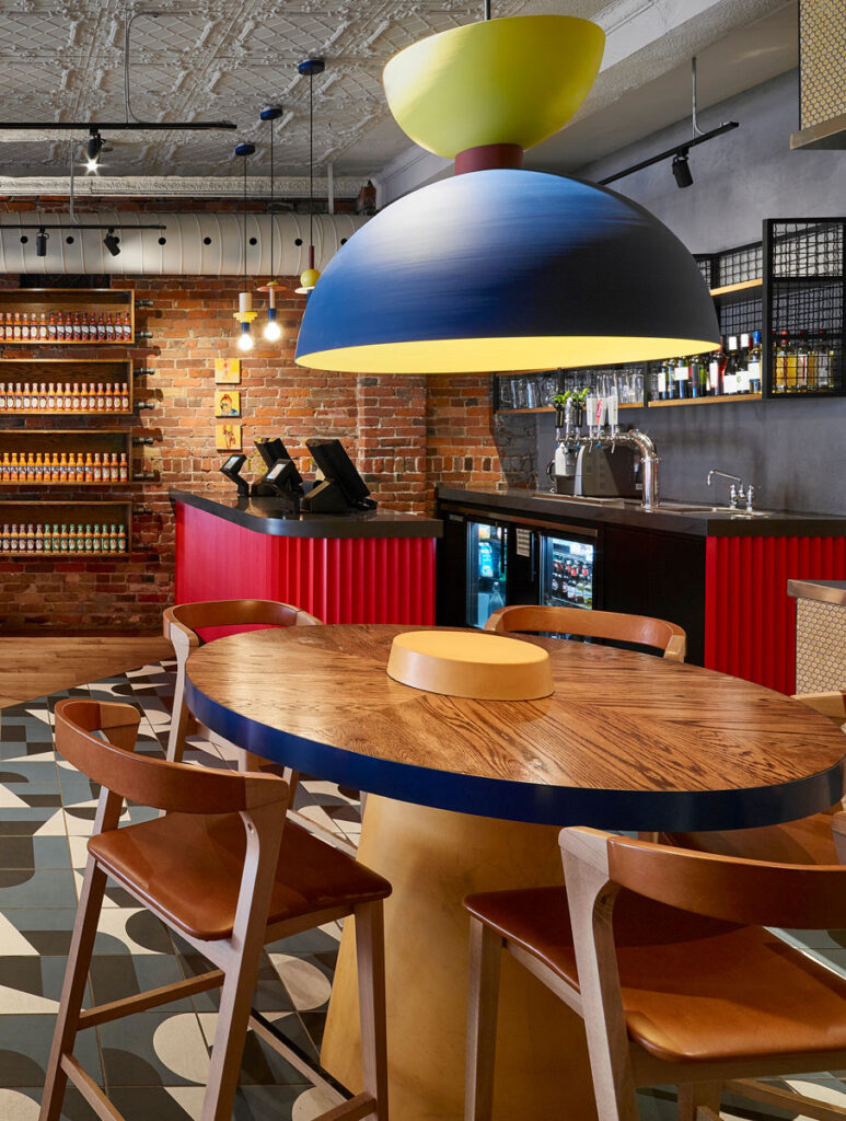 A curved red, yellow and blue light fixture above a round table provides a striking focal point in the space.
