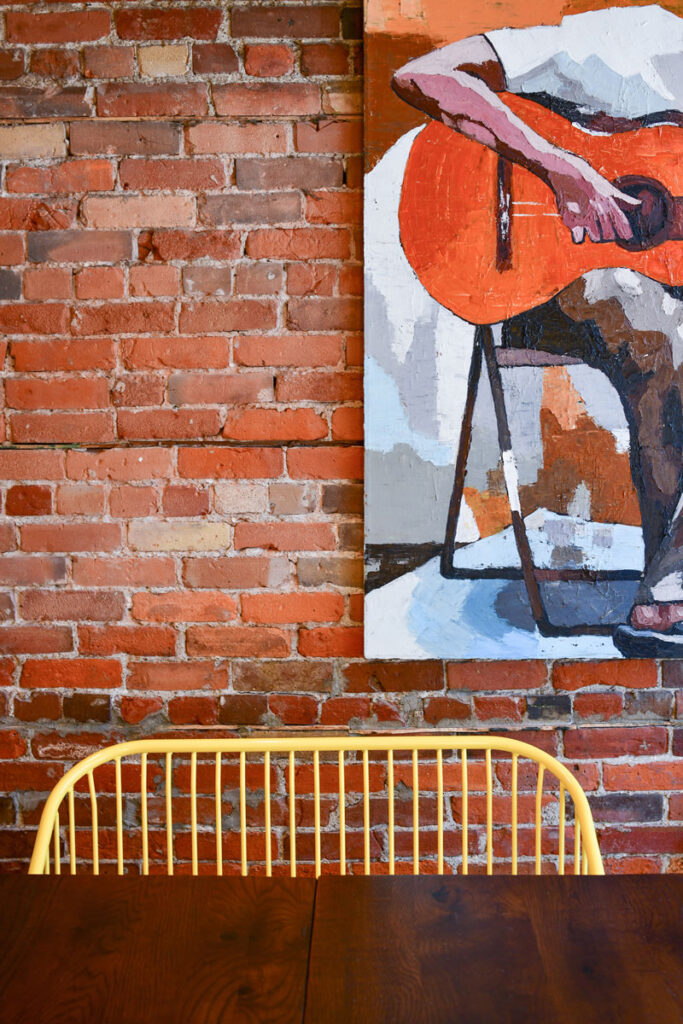 Yellow painted chair against red brick wall with painting in background.