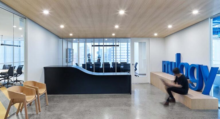 Reception area at Nulogy Corporation with polished concrete floors, a curved black reception desk and branded blue 3D text element.