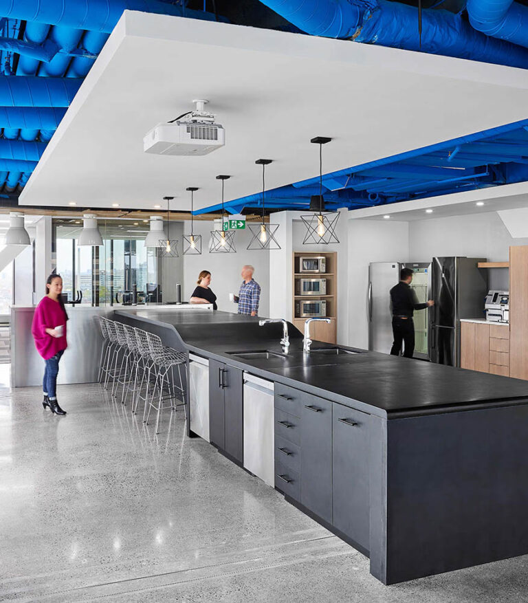 Canteen at Nulogy Coporation with long black high top area. Blue painted ductwork emphasizes the brand colour subtly.