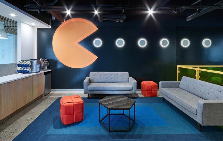 Collaboration lounge at Nulogy Corporation, with grey couches and Pac Man graphic.