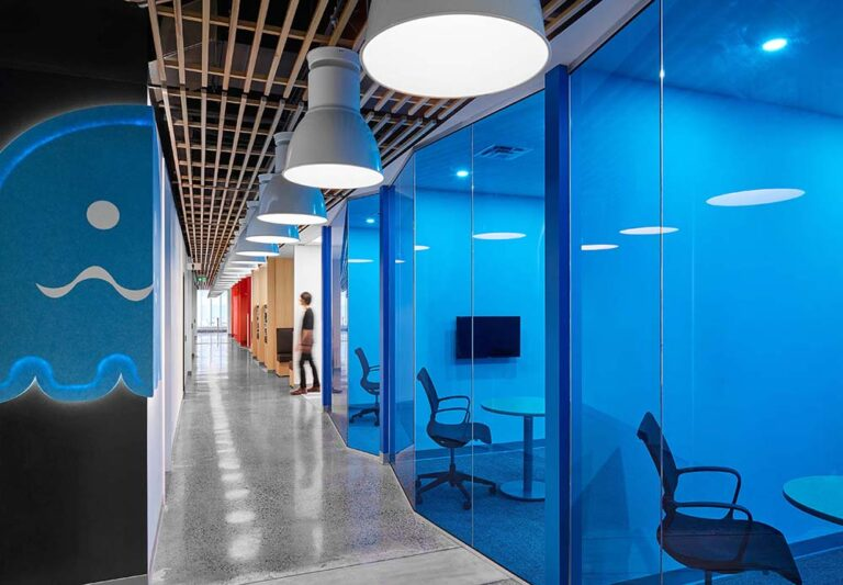Corridor of rooms at Nulogy Corporation with moveable glass walls with a transparent blue film to emphasize the brand colours.