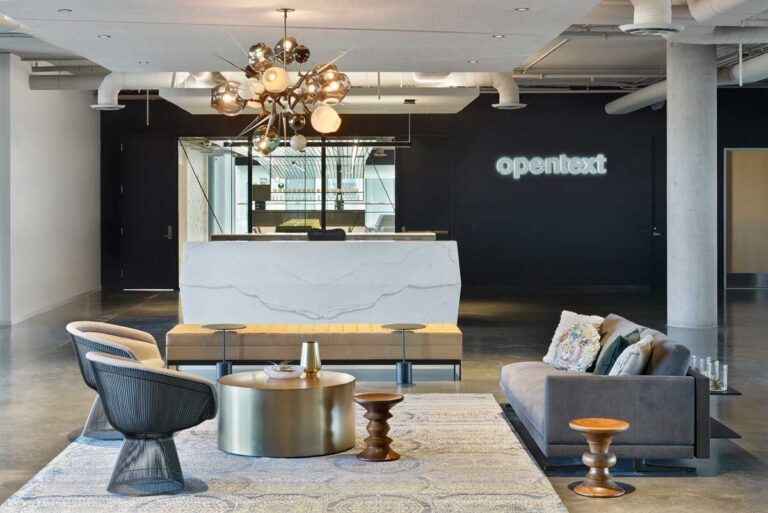 Reception area at Open Text with gray and slate seating area with glass and steel light fixture.