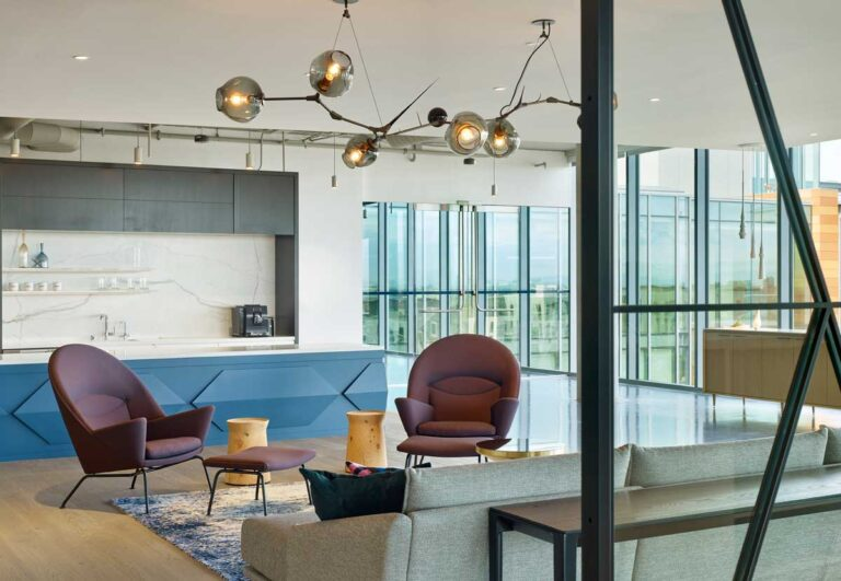 Seating area in an open plan office with gray couch and maroon chairs, a glass and steel light fixture hangs overhead.