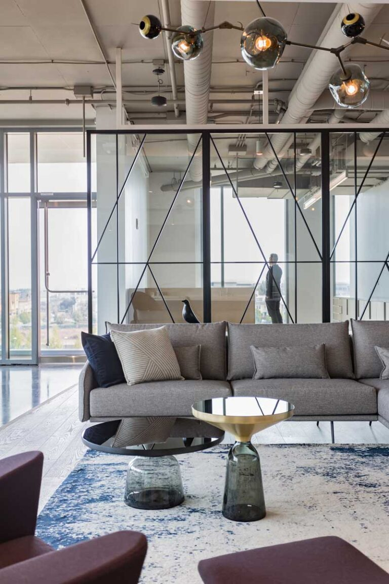 A comfortable modern seating area is a calming space in a software office with couch and glass topped tables.