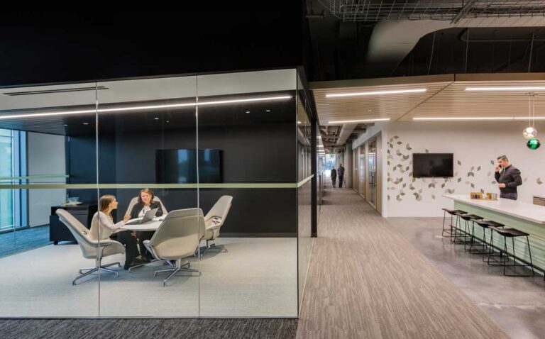 Glass walled modern office with round meeting table next to employee workspace.