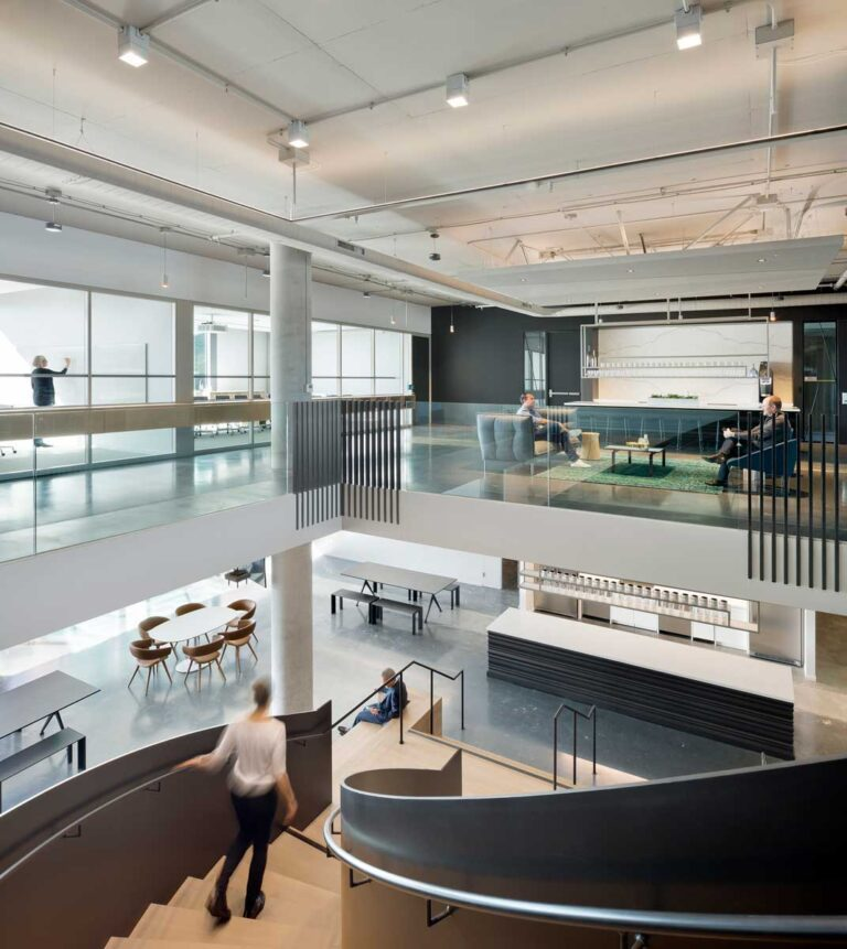 View from top of curving stairs which connect two floors in this bright modern office.