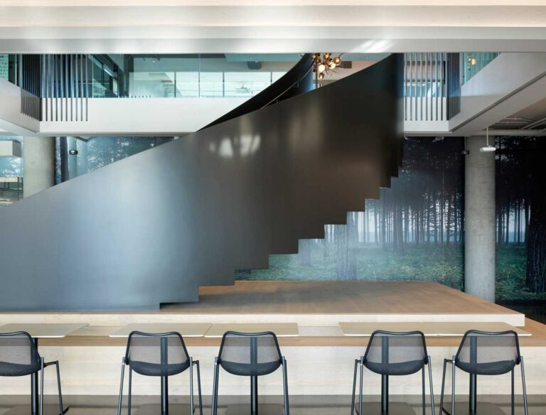 Employee workspace with high top tables is placed next to the curving feature stair.