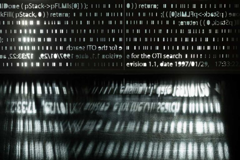 A perforated metal screen pattern displays the foundational software code on which Open Text was built.