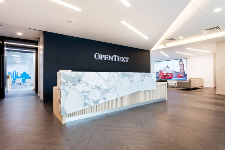 Reception area at Open Text Reading offices with tambour wood behind a beautiful slab of grat and white marble.