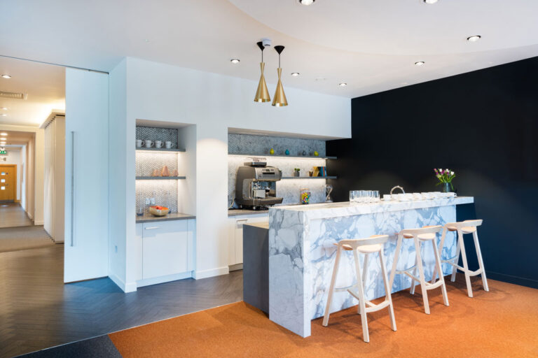 Employee cafe area extends the gray, black and white brand colours with metallic touches.