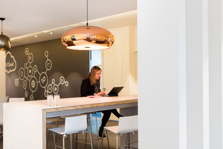 An employee works on a laptop in the cafe area with a bronze coloured lamp overhead.